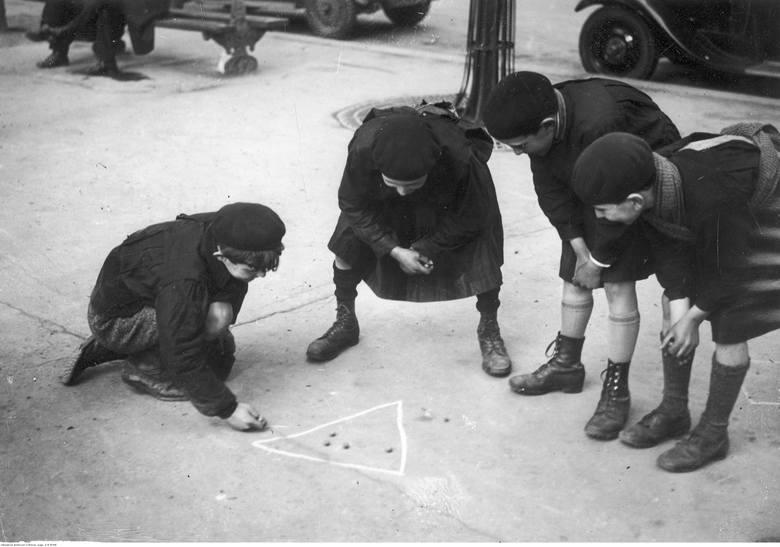 Uczniowie w mundurkach szkolnych podczas gry w kulki.