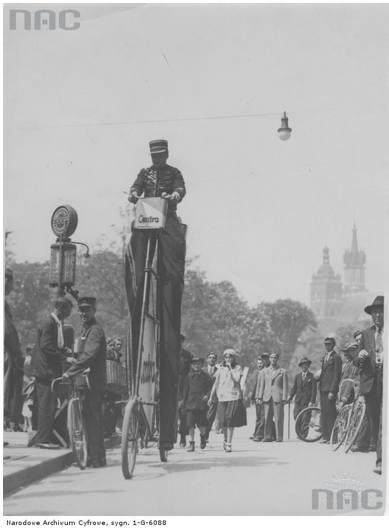 """Reklama baterii """"Centra"""" - przejazd akrobaty na wysokim rowerze w Krakowie (1922).http://www.audiovis.nac.gov.pl/obraz/95264/db50b"""