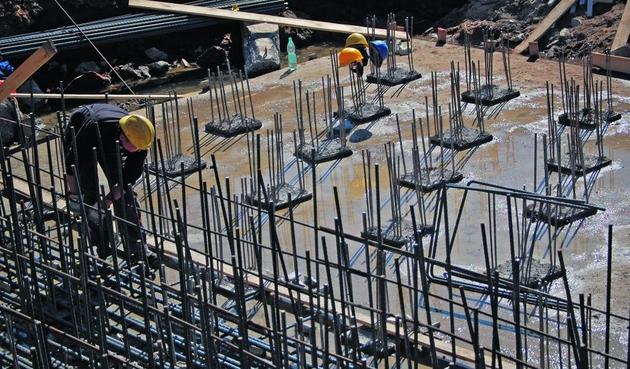 Robotnicy zbroją stopę fundamentową pod podporę estakady prowadzącej do mostu