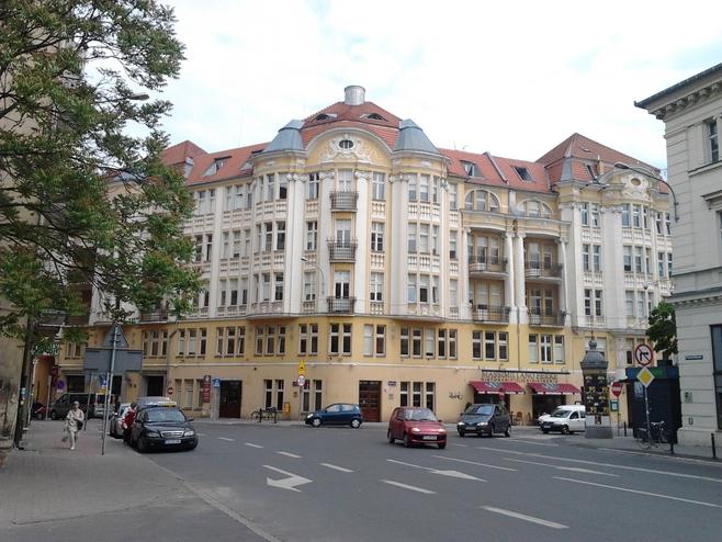 Kamienicę u zbiegu Placu Wolności i ul. 3 Maj zaprojektował Roger Sławski, poznański architekt, którego imię nosi Technikum Budowlane i Zasadnicza Szkoła