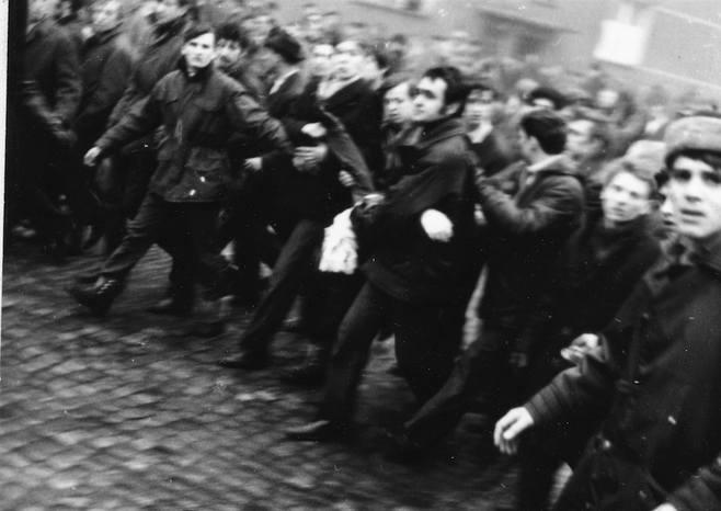 Zdjęcie zrobione 17 grudnia 1970 r. na ulicy Czerwonych Kosynierów w Gdyni. Budynek w tle to prawdopodobnie ul. Morska 51, czoło pochodu z ciałem Zbigniewa