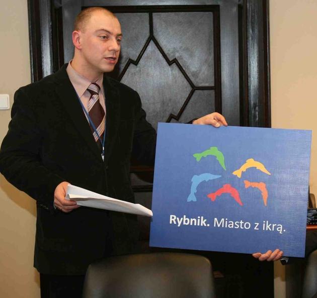 Krzysztof Jaroch prezentuje tablicę z nowym logo