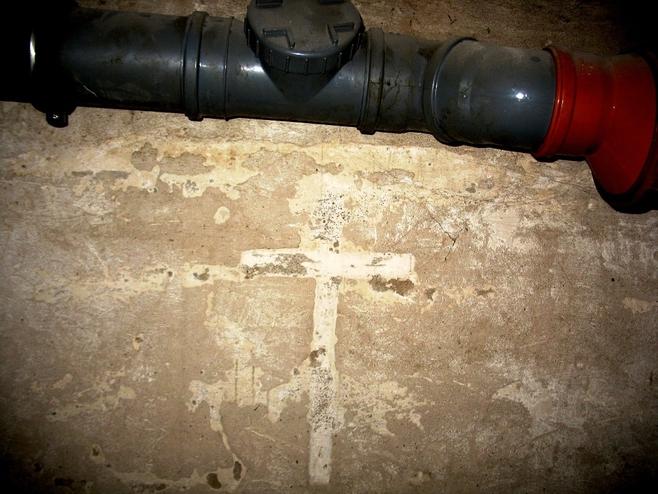 W jednej z byłych cel w piwnicach pozostał na ścianie krzyż wyżłobiony przez więźniów