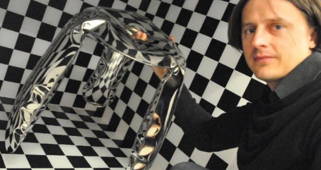 Oskar Zięta z projektem pokazanym w październiku w Wiedniu. Wzory ze ścian konstrukcji z pleksi odbijają się na taborecie w taki sposób, że widz traci poczucie, co jest naprawdę, a co widzi przez chwilę (fot. Paweł Janczaruk)