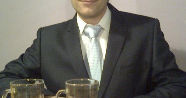 Sebastian Łaźniak prezentuje kubek, który został doceniony podczas konkursu na start-up