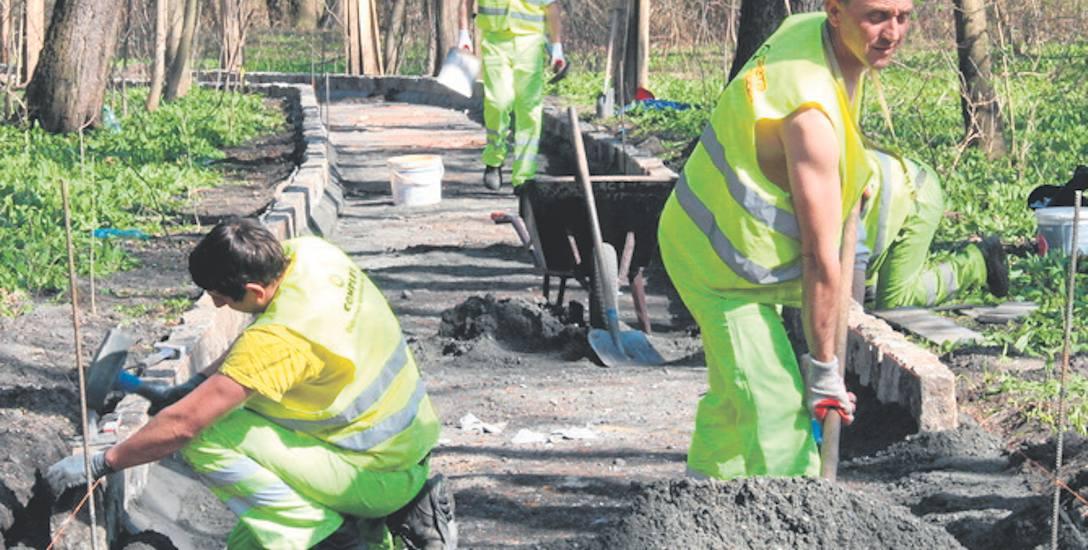 Pracownicy firmy Gretasport układają m.in. nowe krawędzie chodników, wykorzystując wyczyszczone kamienne obrzeża