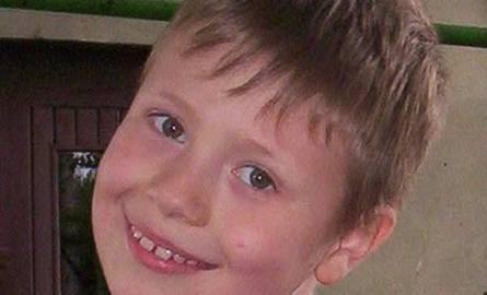 Enrico Bevilacq ma 8 lat. 140 cm wzrostu, szczupły, włosy blond, grzywka czesana na czoło, oczy zielone. Miał na sobie czerwono-popielatą bluzę z czerwonym