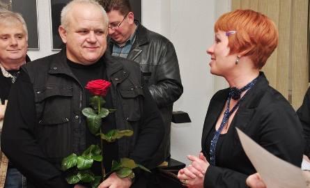 """Przemysław Barański otrzymał na wernisażu piękny kwiat od Magdaleny Grzyb, szefowej """"Łaźni""""."""