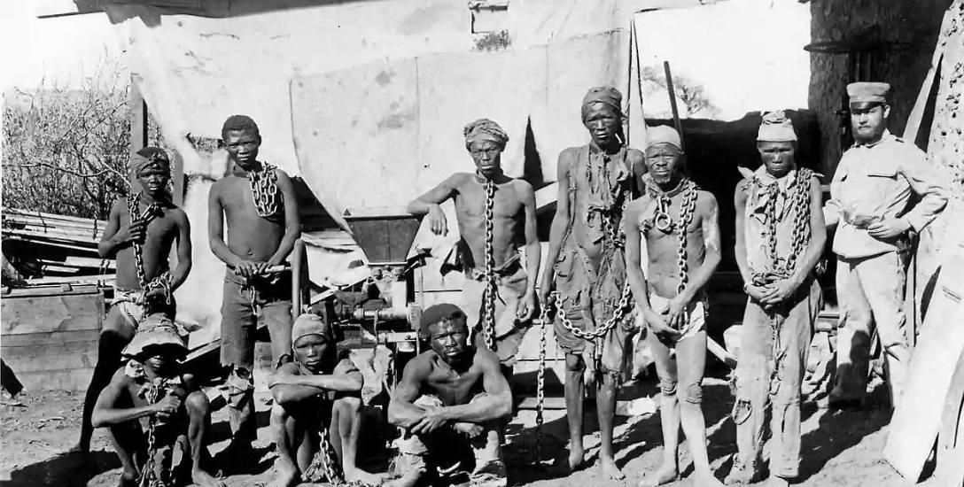 Niemiecki żołnierz i zakuci w kajdany Hererowie