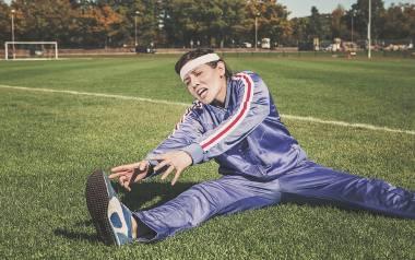 Kobieta w niebieskim dresie rozciąga się na zielonej trawie.