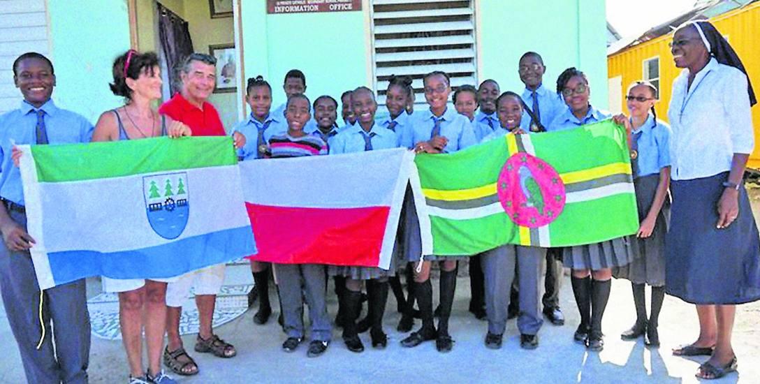 Maria Kaminski z mężem Jean-Paulem w szkole w Portsmouth. Trzymają flagę Czerska. Uczniowie mają natomiast dwie flagi: Polski i Dominiki. Z prawej siostra