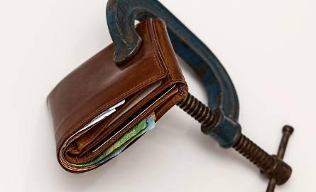Na zdjęciu: zaciśnięty portfel, symbol tarczy antykryzysowej (tarczy 4.0)