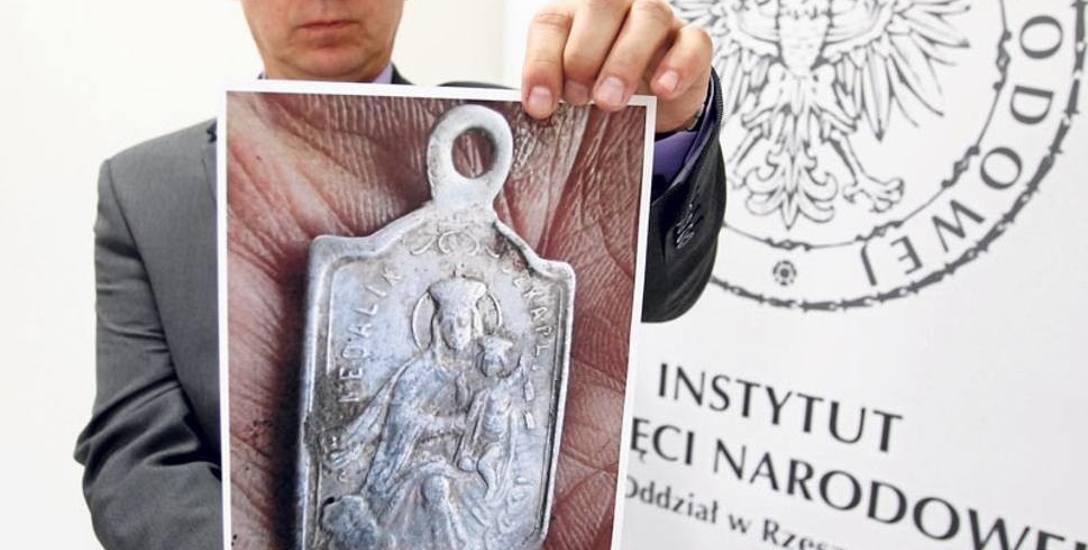 Prokurator Grzegorz Malisewicz prezentuje zdjęcie jednego ze znalezionych przy ludzkich szczątkach szkaplerzy z wizerunkiem Matki Bożej z Dzieciątki