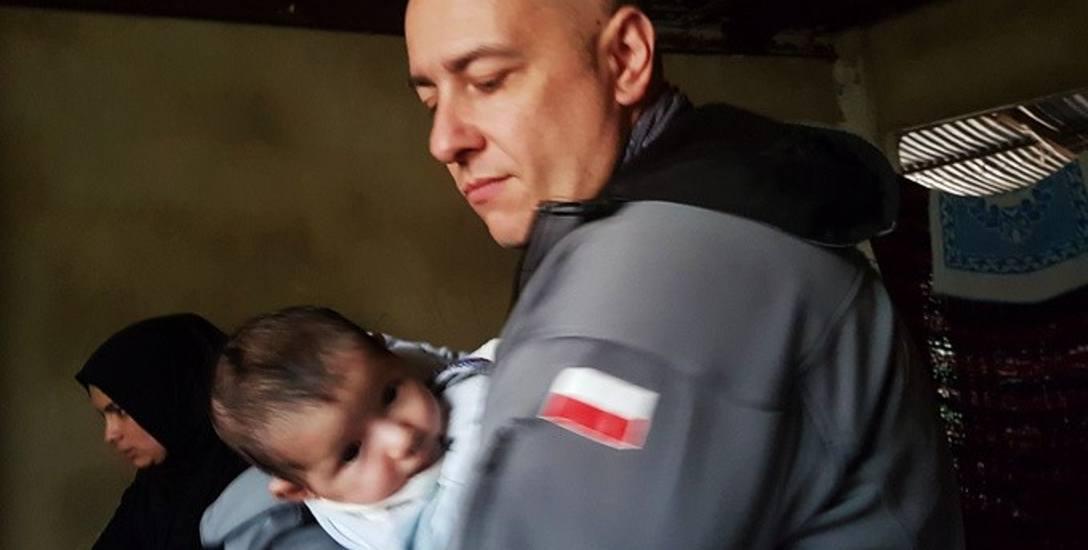 W Libanie lekarz odwiedzał chorych w obozowiskach. Na zdjęciu z dwumiesięcznym niedożywionym niemowlęciem.