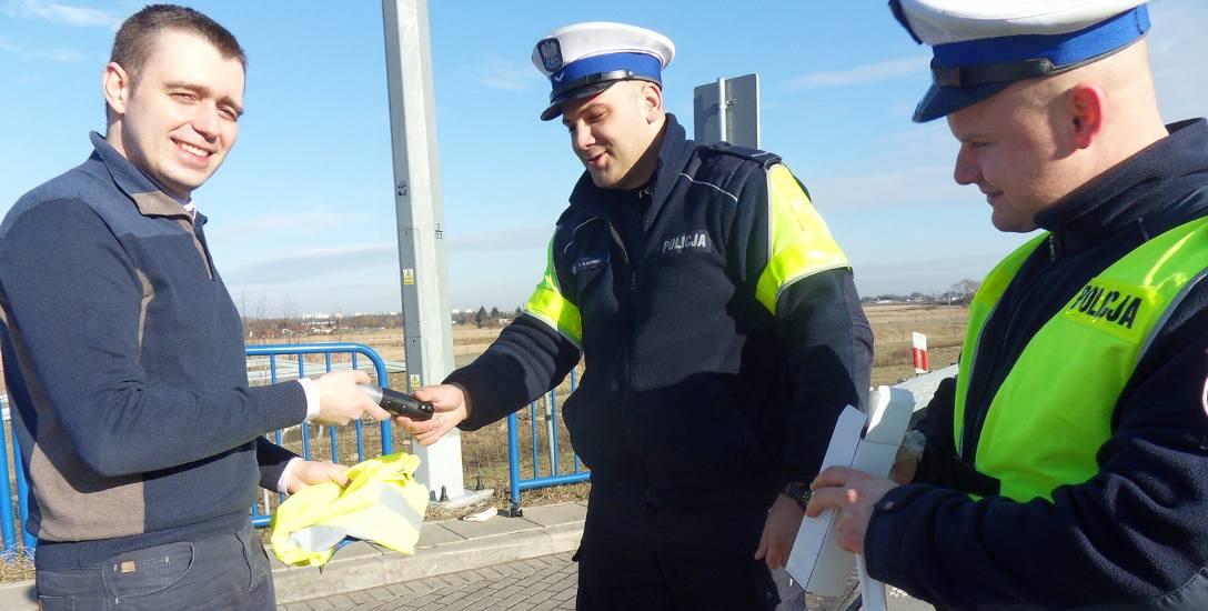Maciej Król spod Świecia otrzymał od policjantów : sierż. Kajetana Kaminskiego i st. sierż. Sebastiana Kowalika (od prawej) ulotkę informującą o zasadach