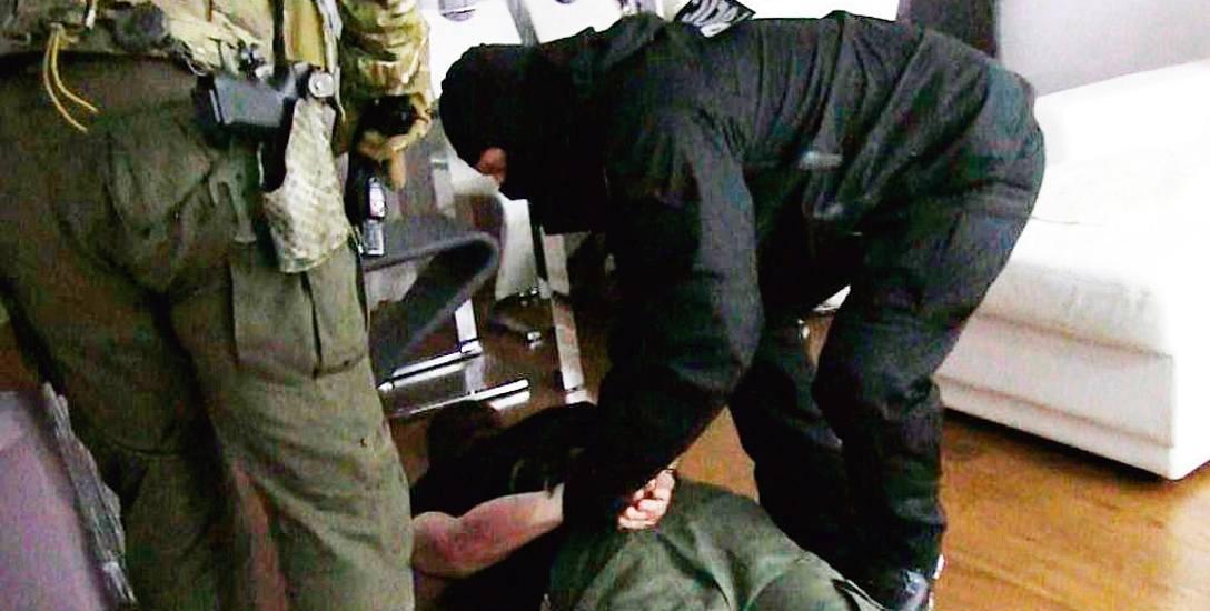 Zdjęcie z zatrzymania przez CBŚP członka gangu podrabiającego perfumy i markową odzież. Podczas  zabezpieczania przez CBŚP magazynów spora część lewych
