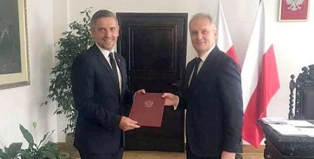 Tomasz Czerwiński (z lewej) odbiera nominację z rąk wojewody Dariusza Drelicha