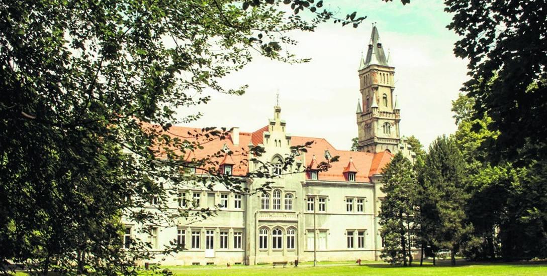Pałac Donnersmarcków w Nakle Śląskim. Budynek jest otoczony niedużym parkiem w stylu angielskim i właśnie jest to widok od strony tego parku.