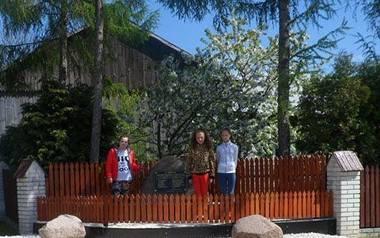 Uczniowie Szkoły Podstawowej imienia Jana Brzechwy w Ratajach Słupskich w powiecie buskim przed pomnikiem upamiętniającym przysięgę złożoną przez członków