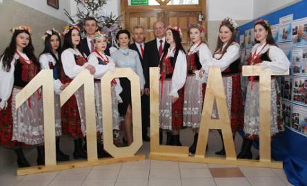 Szkolny zespół ludowy, a w środku przedstawiciele szkoły z burmistrzem Waldemarem Grochowskim