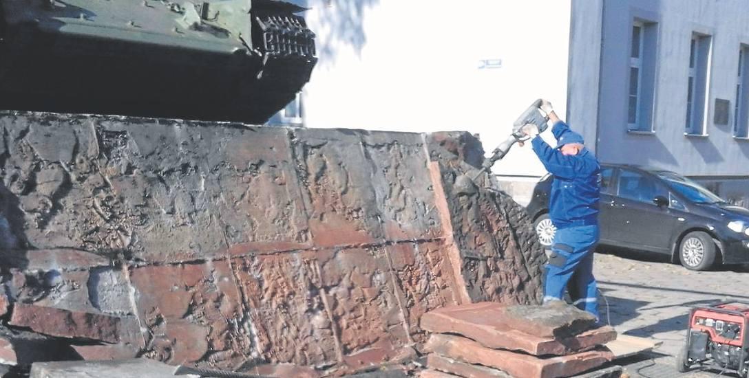 Pracownik Zakładu Usług Komnunalnych usuwa za pomocą młota pneumatycznego jeden z reliefów. Zdaniem Eryka Krasuckiego taki sposób działania to barbarzyństwo.