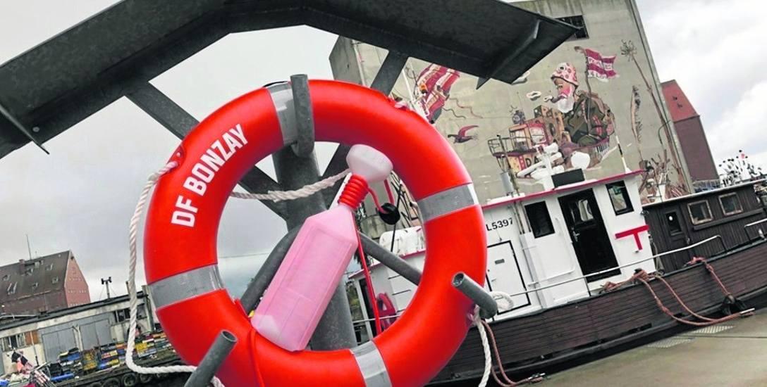 Koła ratunkowe zawisły nad kanałem portowym w Darłowie, obok którego przechodzą spacerowicze i przejeżdżają rowerzyści