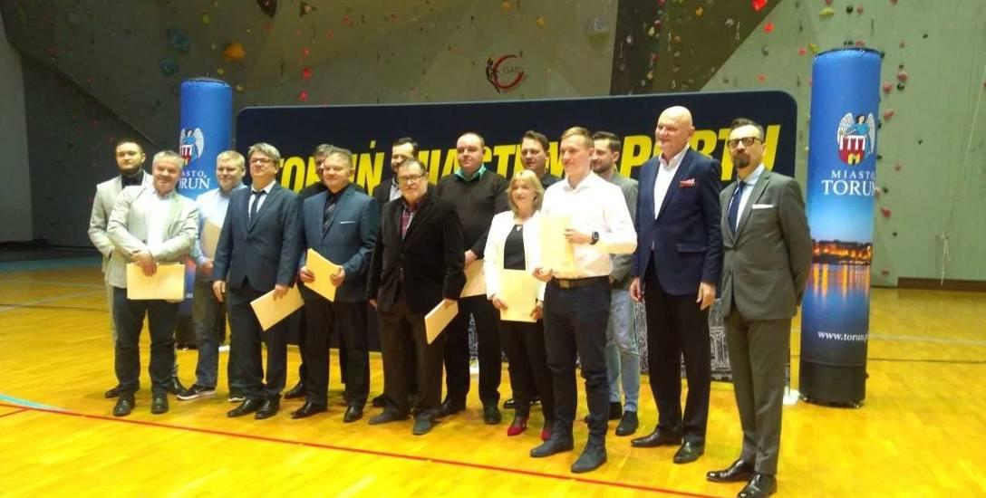 Na środku: Stanisław Momot i syn Tomasz wraz z prezydentem Torunia i nagrodzonymi.