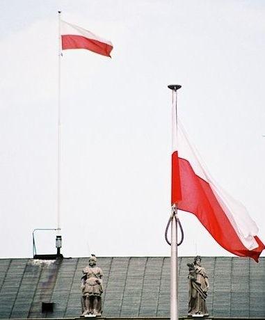Flagi Polski przed i na Pałacu Prezydenckim w Warszawie