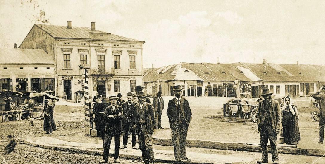 """Rynek w Zabłotowie - z niewybrukowanym placem i parterowymi domkami, w tle sklep Myslowitza i restauracja """"Bilard"""", pocztówka z ok. 1910 roku. Ze zb."""