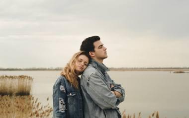 Na zdjęciu para: mężczyzna patrzący na jezioro i kobieta pochylająca twarz na jego plecach