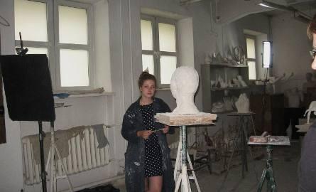 Maria patrzy smutno na rzeźbę.