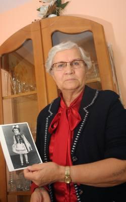 Lidia Skibicka-Maksymowicz trzyma w ręku swoje zdjęcie zrobione niedługo po wyjściu z obozu Auschwitz