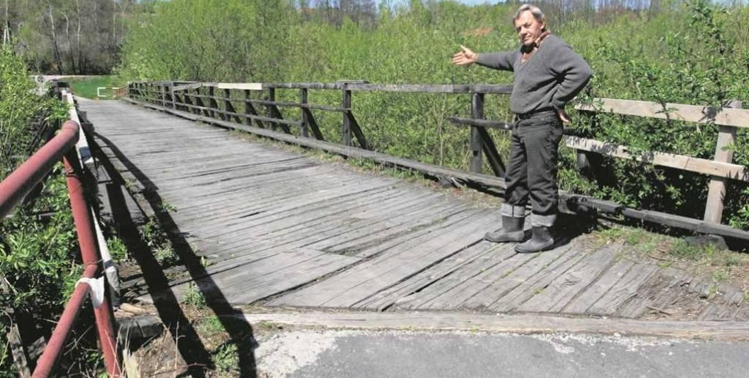 Piotr Bułat wskazuje na fatalny stan techniczny mostu w Kamyku. Jeszcze rok temu jeździły tędy samochody. Od 7 lipca 2017 roku obiekt stoi zamknięty.