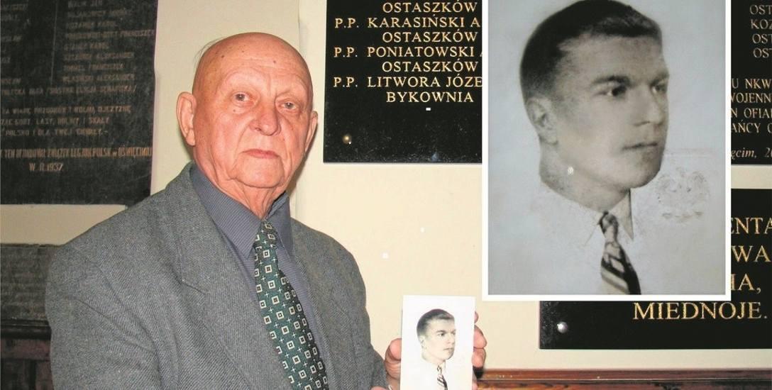 Marian Bartel z fotografią swojego brata przed pamiątkową tablicą w kościele parafialnym w Oświęcimiu