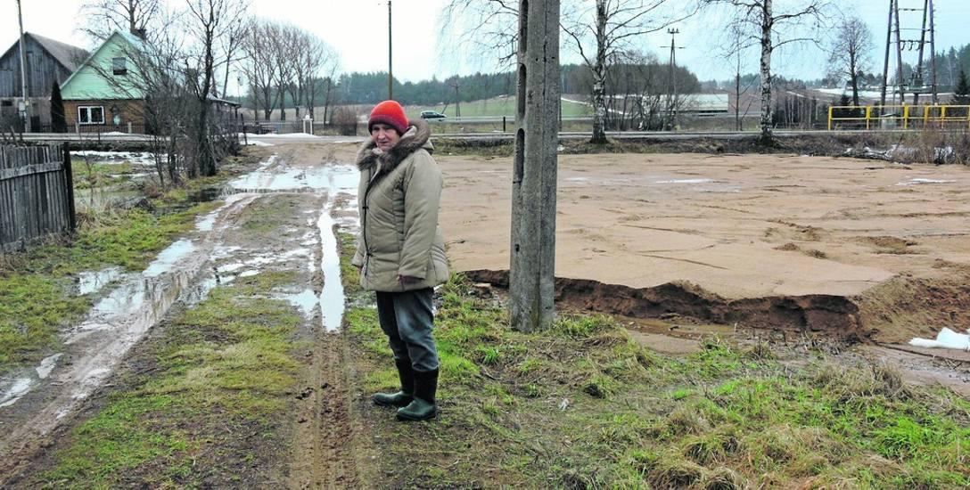 Stanisława Klej przy drodze, na której przez budowę placu zabaw stoi stale woda.