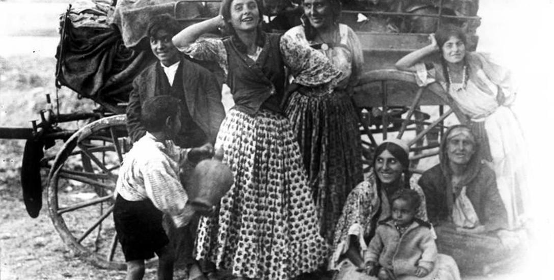 Rodzina cygańska na tle tradycyjnego wozu.
