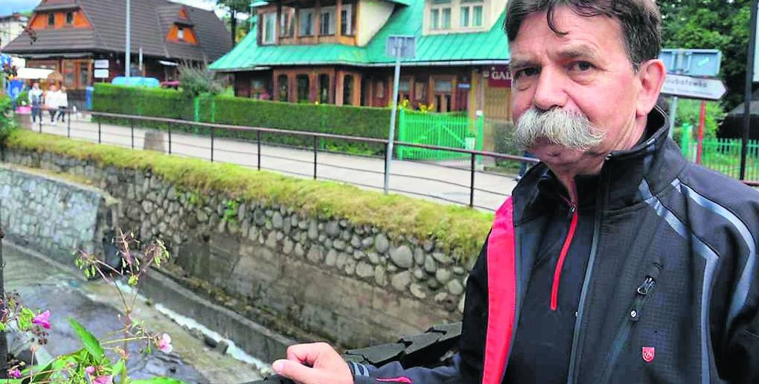 Radny Jerzy Jędrysiak pokazuje zawalony mur w potoku (za jego plecami). Runęło ok. 20 metrów
