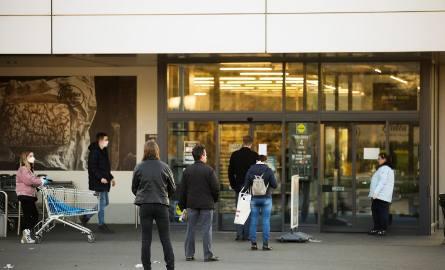 Kraków - kolejka przed sklepem w którym może przebywać tylko trzy razy więcej klientów niż jest kas.