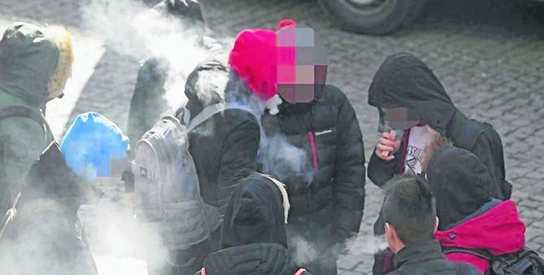 Młodzież paląca papierosy przy sklepie w okolicy mechanika