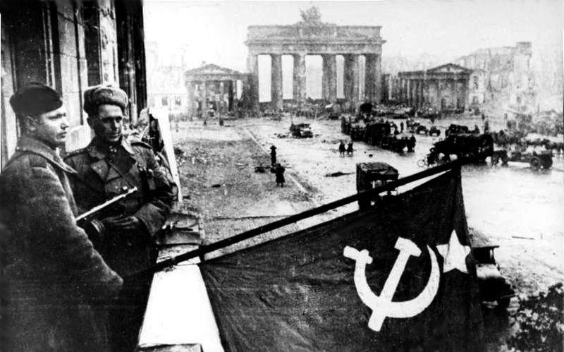Żołnierze radzieccy wywieszają flagę Związku Radzieckiego na balkonie hotelu Adlon, w tle Brama Brandenburska