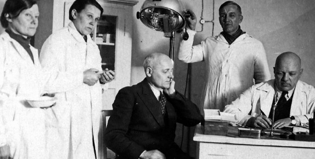 """Dr Stanisław Bełdowski (siedzi za biurkiem) z personelem szpitala """"epidemicznego"""""""