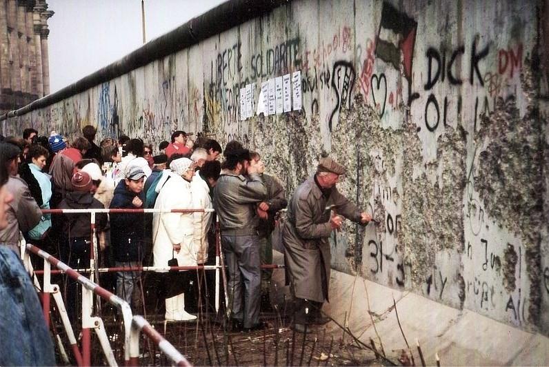 Mieszkańcy Berlina Zachodniego przy mocno zniszczonym murze w pobliżu Reichstagu w końcu 1989