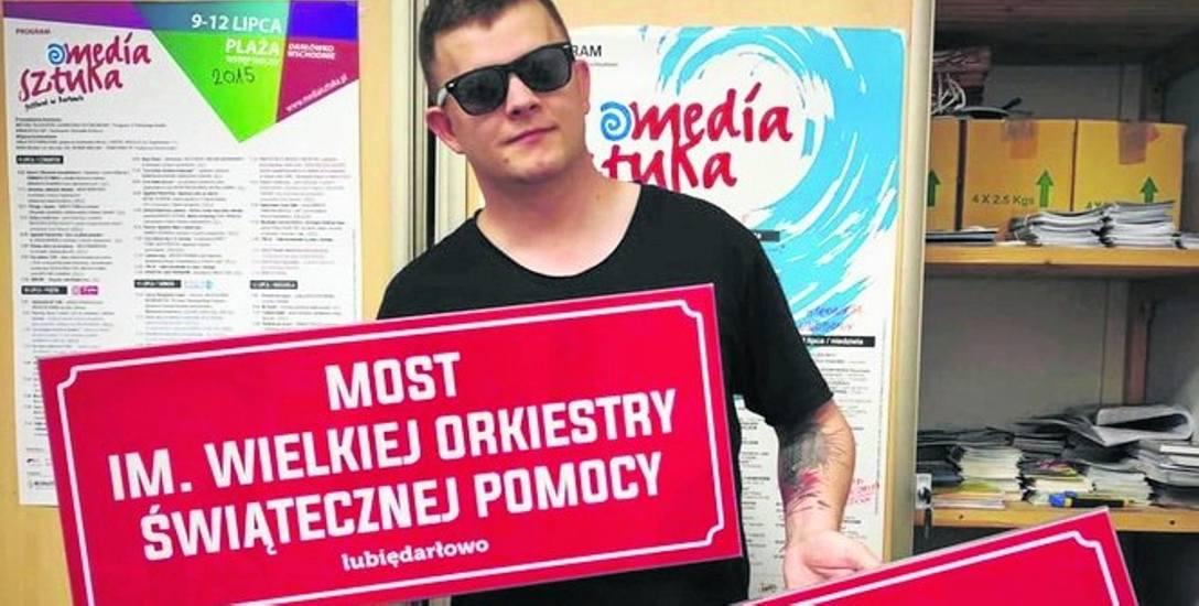 Daniel Frącz, inicjator pomysłu na nazwę dla mostu przy Wyspie Łososiowej pokazuje gotowe tablice informacyjne