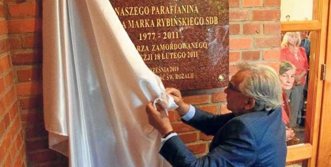 Józef Słupek, przewodniczący rady parafialnej w kościele św. Rozalii, odsłania tablicę
