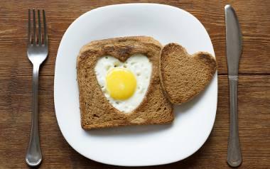 Znanym sposobem na sycące, a już na pewno ciekawe wizualnie śniadanie jest wykrojenie w kromce foremką np. kształtu serca, ułożenie jej na patelni i