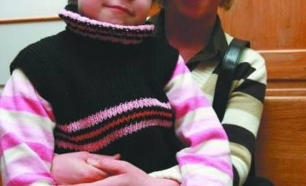 Siedmioletnia Sylwia tuli się do mamy. Mimo wszystko uśmiecha się do nas. Choroba u dziewczynki dała o sobie znać zwykłym bólem brzucha. Sylwia leczy