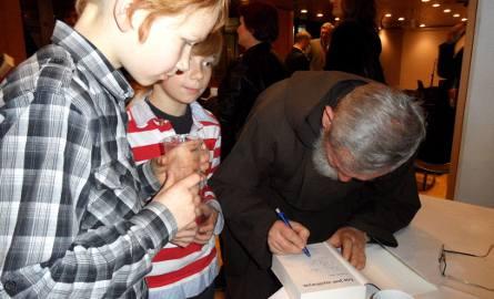 Ojciec Dominik, kapelan wszystkich lotników, podpisuje autografy młodym czytelnikom