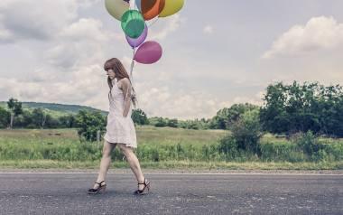 Smutna, kobieta wędruje w samotności z balonikami.