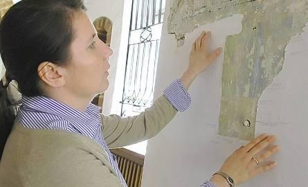 Danuta Miliszewska ogląda polichromię znalezioną pod warstwami tynku w świebodzińskim ratuszu.