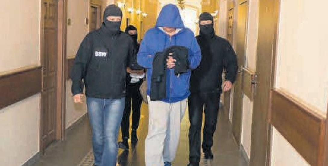 Jeden z aresztowanych policjantów doprowadzany w sądzie. Podejrzani są już na wolności. Grozi im do 10 lat więzienia.